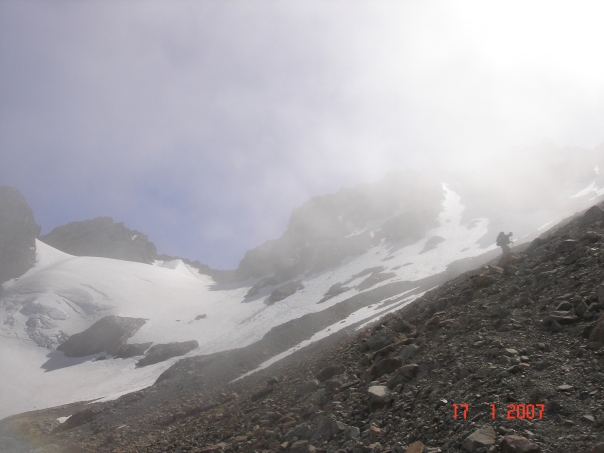 A climber traverses around towards Ball Pass in the mist.