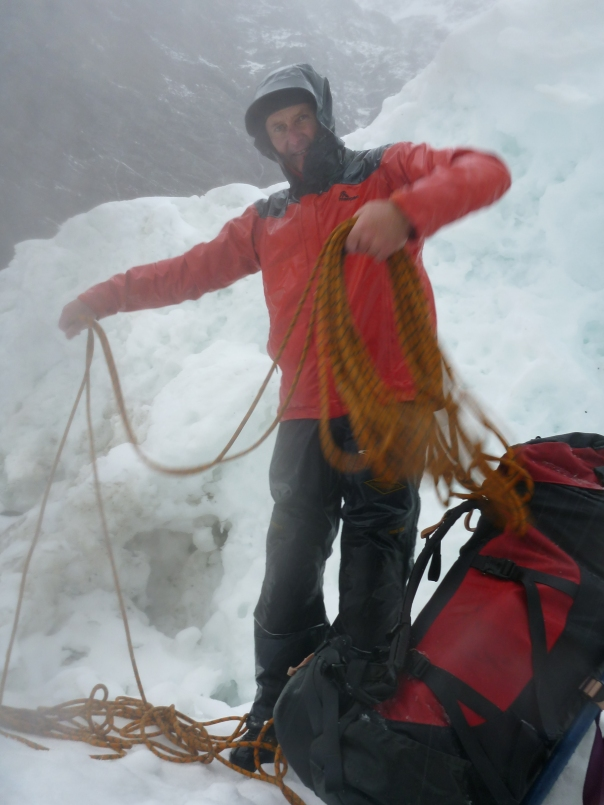 A cold and wet Alan Silva coils the rope as we prepare to leave in the morning.