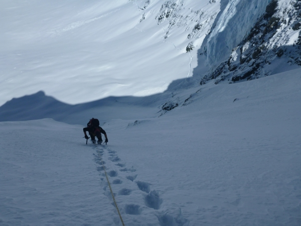 Alan Silva climbing the steep snow slopes to access Mount Dixon's east ridge