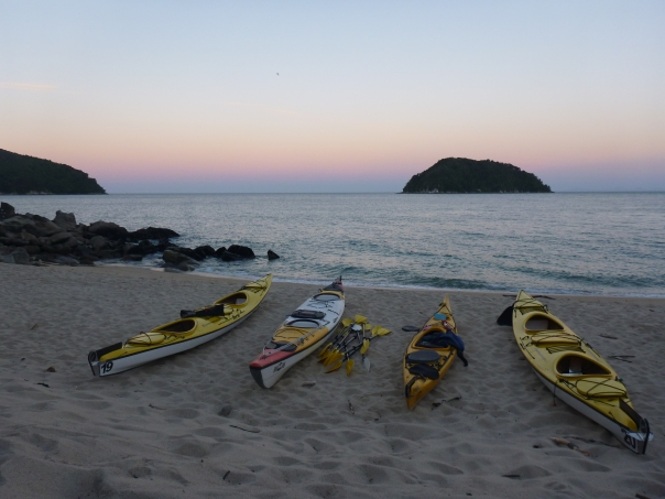 Dusk falls over our kayaks lying on the beach. Tonga Island in the distance.