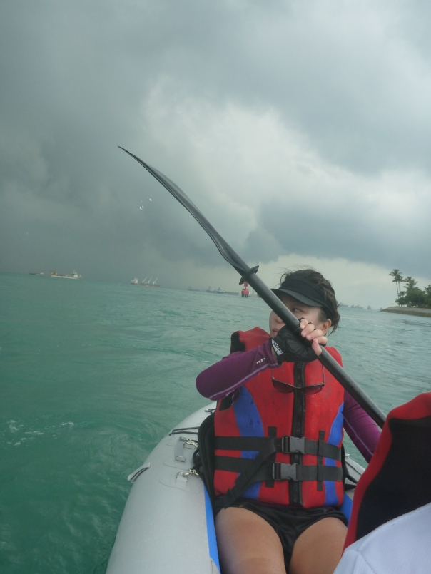 Leaving Tanjong Beach behind and making good time paddling with the current. Some big black clouds behind Stephanie's shoulder would eventually catch us out later.