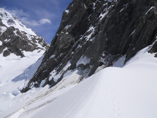 Me crossing the top of the Boys Glacier and about to head down under the dangerous slopes under the Anzac Peaks, note the rock fall and Avalanche debri on the slopes.