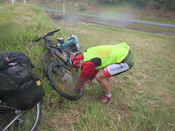 Fixing the first flat tyre in the rain after  20km.