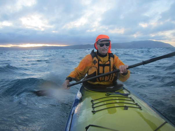 Alan Silva about 2 hours into the paddle, the sunrise and Makara beach Wellington behind him.