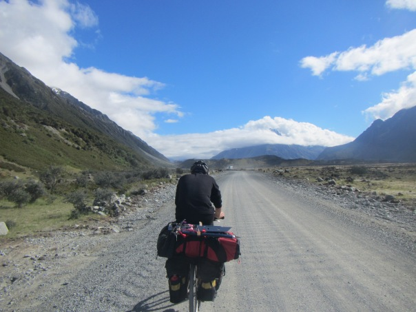 Alan Silva cycling up the Tasman Valley Road with his climbing pack strapped to  the back of his bike.