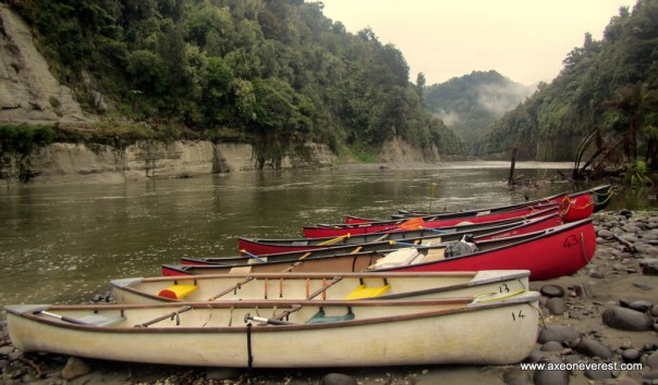 Canadian kayaks line the banks of the Whanganui river.