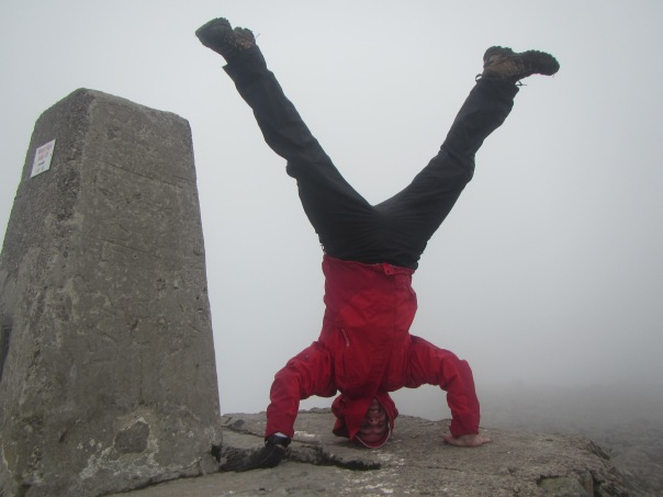 Pulling a headstand on the summit in the cloud.
