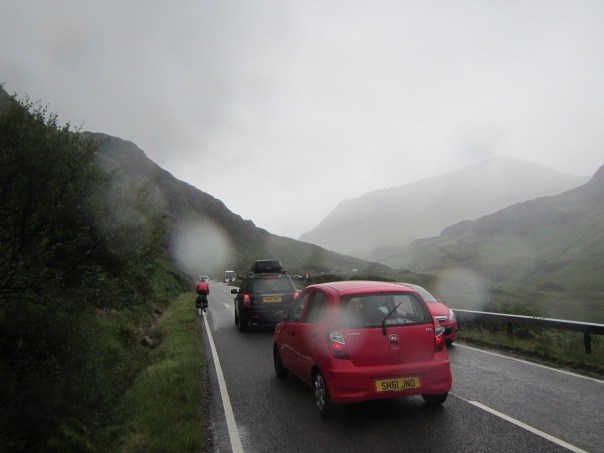 Alan Silva cycling through Glen Coe in heavy rain and traffic