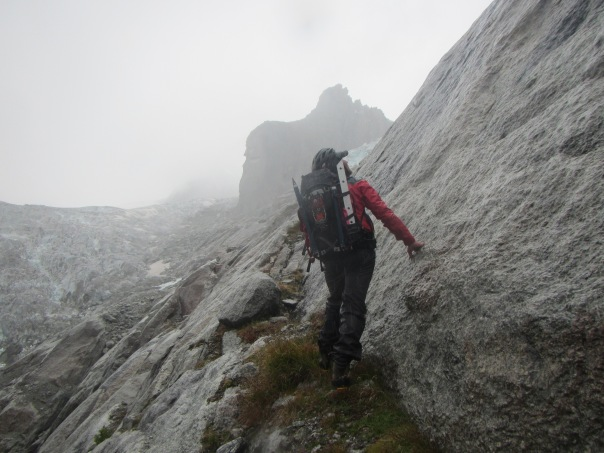 Alan Silva searching for a route up the rock buttress in the rain on day one of the climb