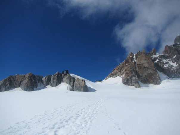 Walking up the Valley Blance - a microwave oven of reflected sun off the snow and heat... The Refuge Cosmiques is on the left rock pinnacle while Aguille du Midi cable station is on top right side - 3800m