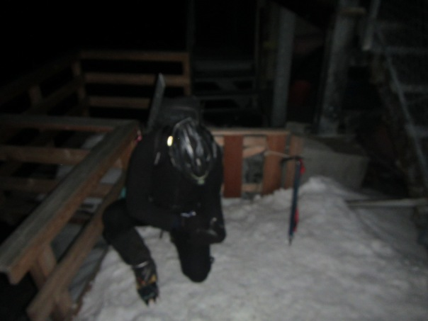 Alan straps on crampons at 3AM for our final push for the summit.