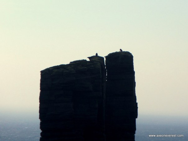 Two German climbers on their knees on the summit of the Old Man of Hoy in strong winds