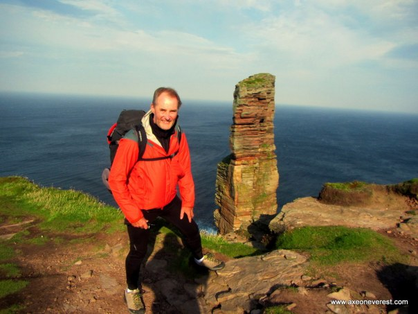 Alan Silva standing on the sea cliffs in strong winds - the summit of the Old Man of Hoy seen behind him.